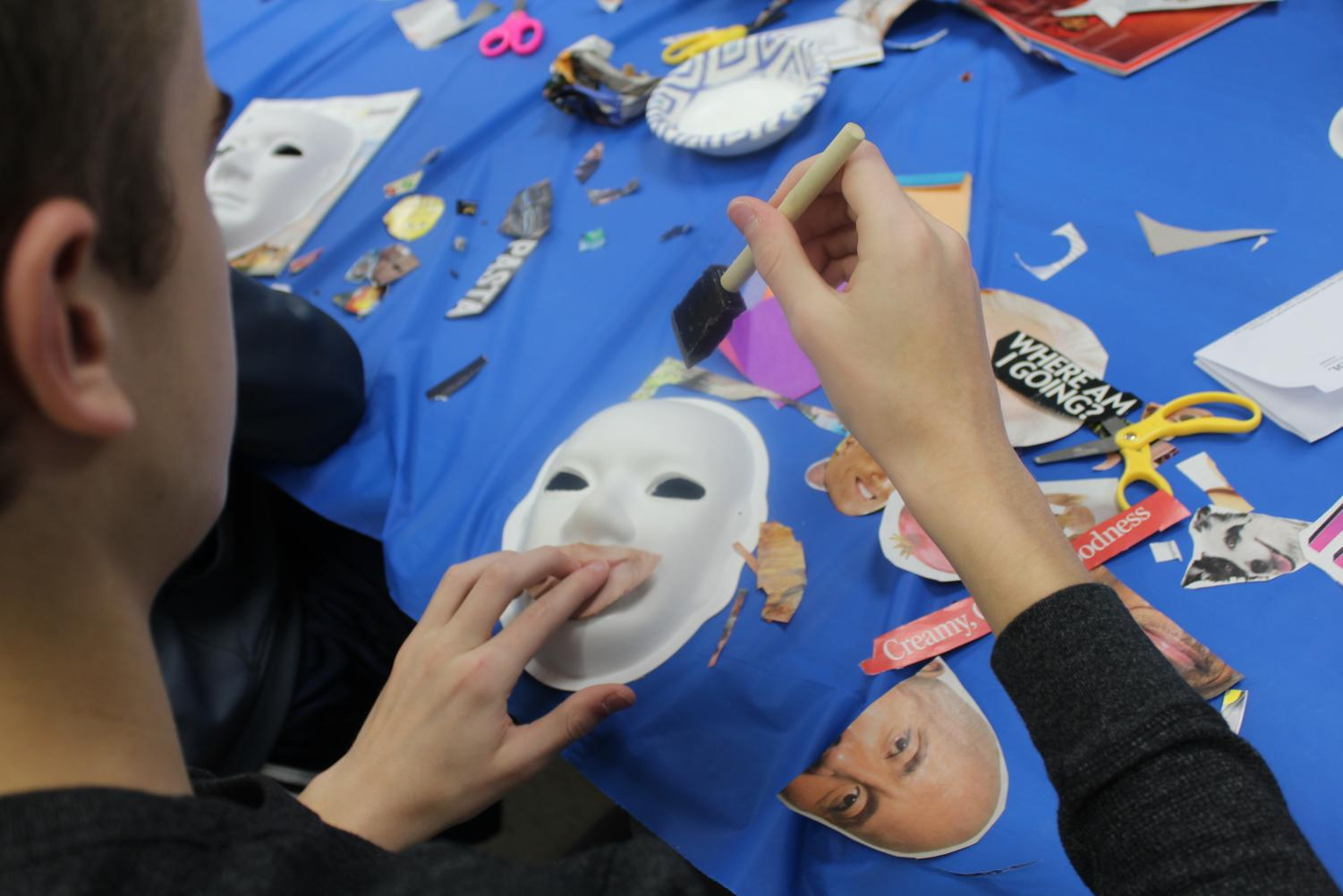 A student participates in creating a mask to represent themselves through images and words.