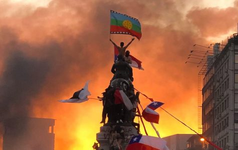 Protester stands at the top of a military statue waving the Mapuche flag, an indeginous group known for their resistance, in Santiago, Chile.