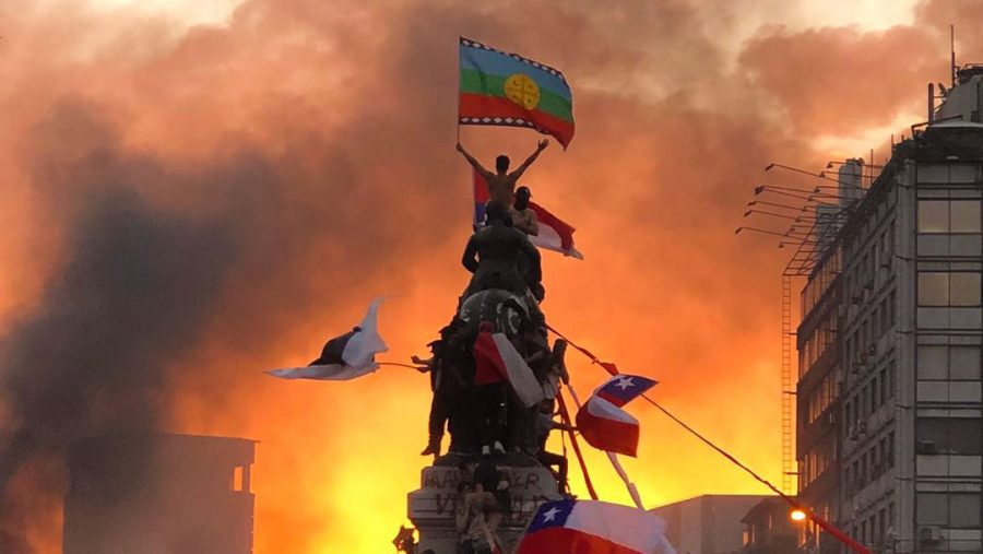 Protester+stands+at+the+top+of+a+military+statue+waving+the+Mapuche+flag%2C+an+indigenous+group+known+for+their+resistance%2C+in+Santiago%2C+Chile.
