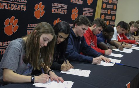 The seniors collectively sign their letters of intent.