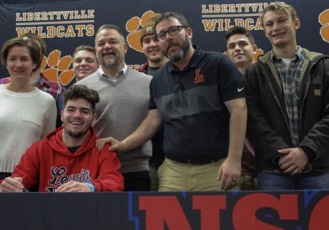 Christopher Boyle, committing to Lewis University for lacrosse, laughs with family and friends after signing his letter of intent.