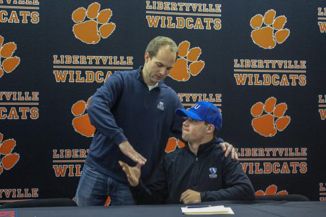 Dylan Drumke shakes hands with one of his coaches, Tim Matheson, after signing
