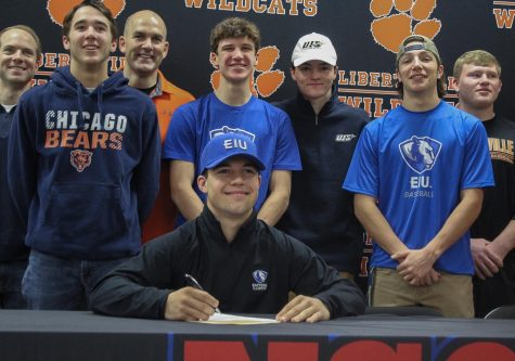 Senior Dylan Drumke's teammates and coaches watch as he signs his commitment to Eastern Illinois University to play baseball in the fall of 2020.
