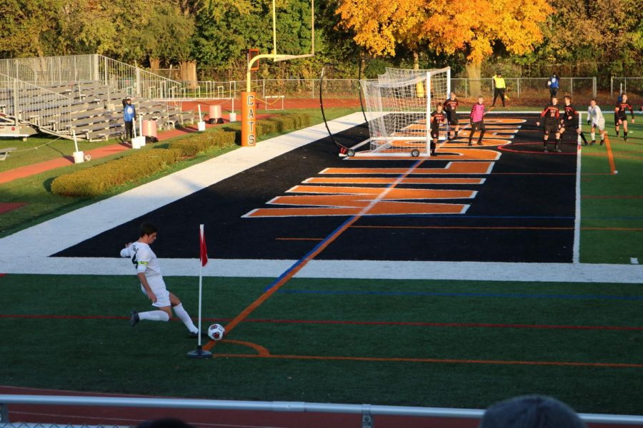 Fremd%E2%80%99s+team+captain+shoots+a+corner+kick+towards+the+Libertyville+goal+while+goalie+Michael+Krukonis+%28in+pink%29+awaits+to+try+to+intercept+the+ball.