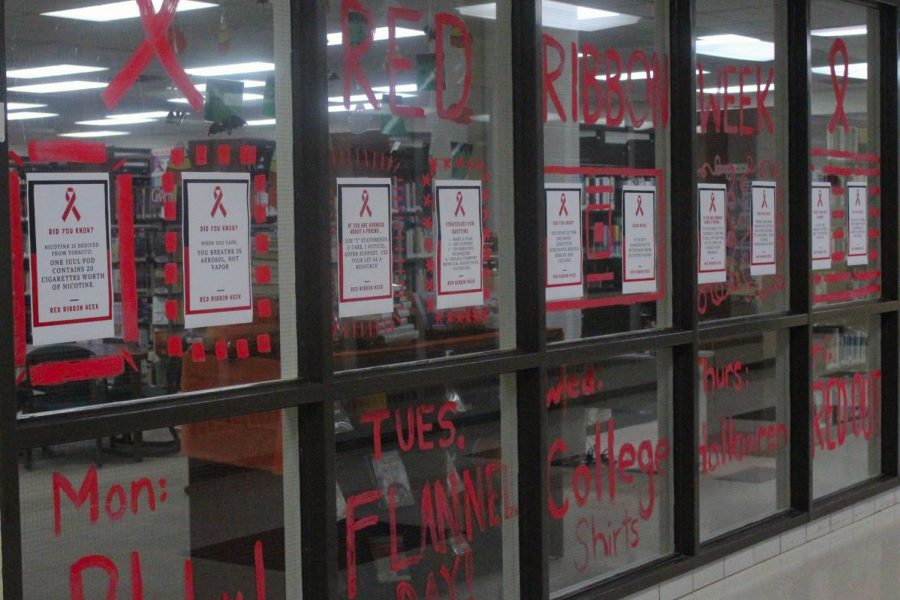 The+Friday+before+Red+Ribbon+Week+started%2C+students+decorated+the+library+and+cafeteria+windows+with+red+paint+and+informational+posters+to+spread+awareness.+