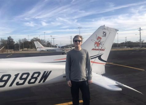 Senior Bradley Larsen has been flying for awhile and has been searching for universities based on their aviation program. Here, he is shown at the University of Oklahoma standing next to one of their many planes.