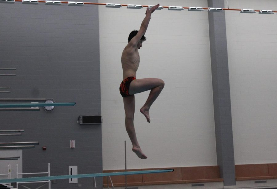 Senior Jake Hughes gains momentum off the end of the diving board.