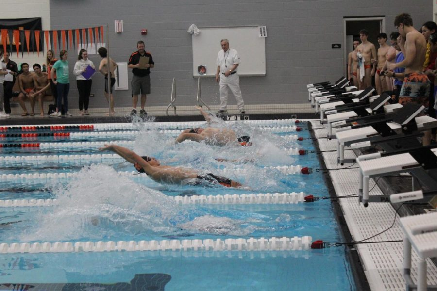 JV swimmers perform a backstroke start to kick off the 200-medley relay.