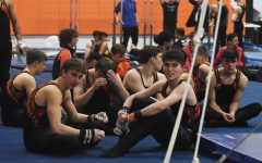 The boys gymnastics team supported their fellow teammates who were competing on high bar.