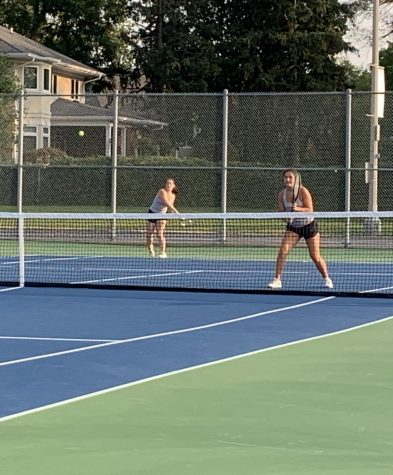 Senior Jenna Zaengle (left) follows through on a shot while her partner, junior Michaela Orvis, prepares for their opponent to hit a return shot.