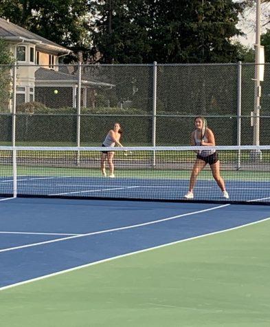 Senior Jenna Zaengle (left) follows through on a shot while her partner, junior Michaela Orvis, prepares for their opponent to hit a return shot.