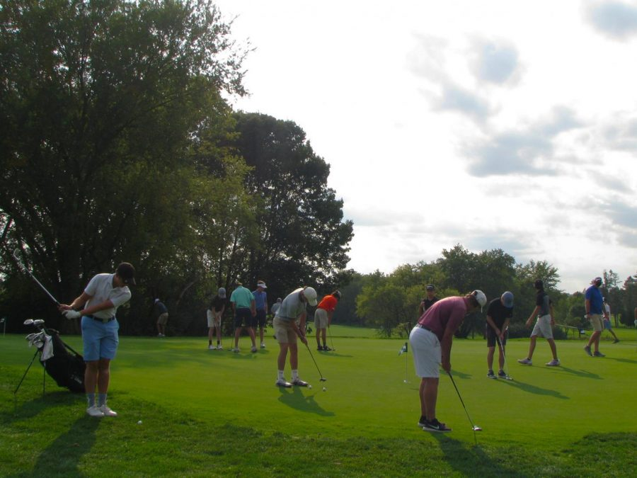 The varsity boys golf team practices putting while six feet apart at Pine Meadow, their home golf course.