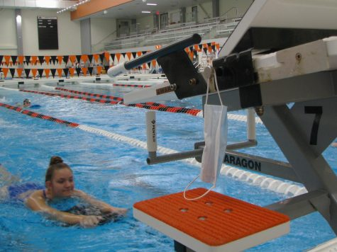A mask hangs on one of the start blocks, as COVID-19 guidelines require swimmers to put on a mask immediately after getting out of the pool.