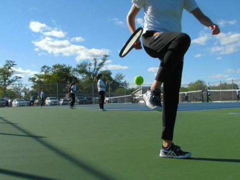 In order to follow COVID-19 guidelines, members of the girls tennis team must pick up balls during practice by capturing the ball in between their foot and their racquet, lifting their leg to bounce the ball, and finally catching the ball with their racquet.