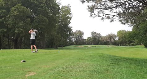 Senior Danny Keating watches his drive down the eighth hole, a par three.