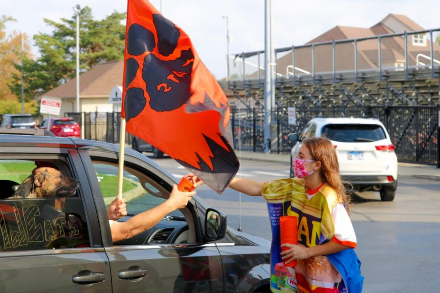 Senior Jane Arnold, wearing a can costume to promote the canned food drive, hands off a Student Council souvenir at the Homecoming drive-through parade.