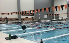 The boys swim team starts practice by hanging their masks on strings before getting in the pool, in order to follow guidelines set by the IHSA.