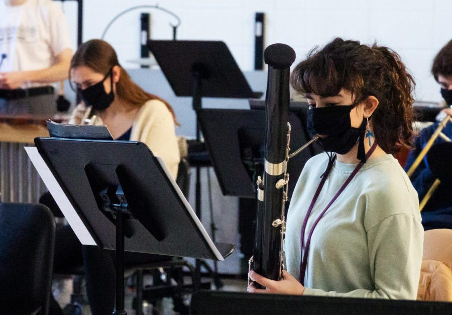 Band students, like Alyssa Abou Chakra, wear masks and have instrument covers to limit the risk of COVID.