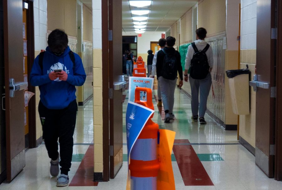 Students pass each other on opposite sides of the hallway, making sure to follow the barrier set in place by social distancing cones.