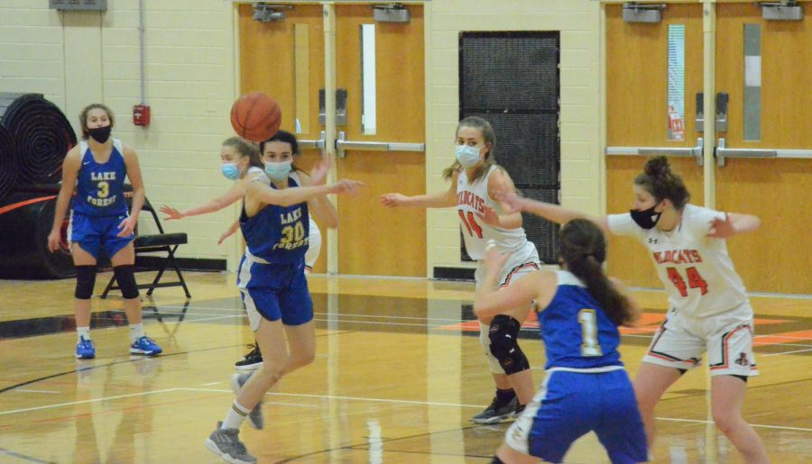 Lake Forest's #30 passes to her teammate while the Cats defend.