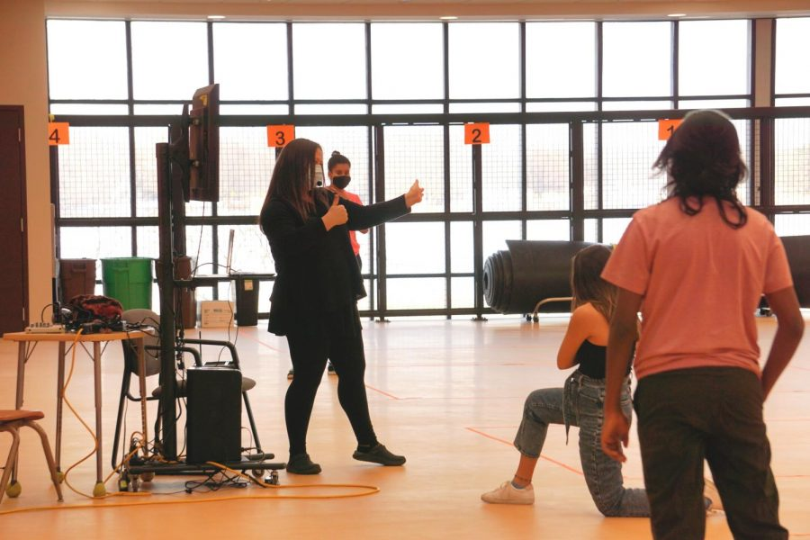 Dance teacher Eryn Brown not only gives directions and critiques to the performers but also makes sure that the rehearsal is following proper safety precautions. A monitor is set up during rehearsal to allow remote performers to watch.