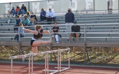 Senior Katie Stone leaps into action over the hurdles as she warms up for her race.