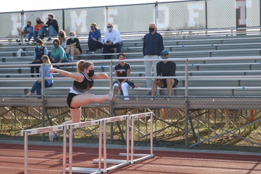 Senior+Katie+Stone+leaps+into+action+over+the+hurdles+as+she+warms+up+for+her+race.