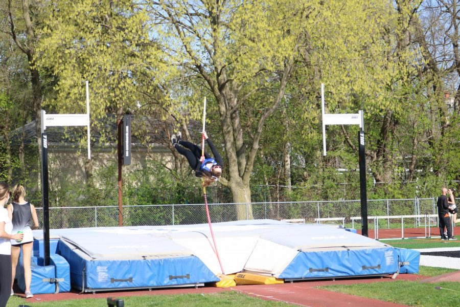 A Lake Zurich pole vaulter practices her jump without the bar early in the meet to warm up.