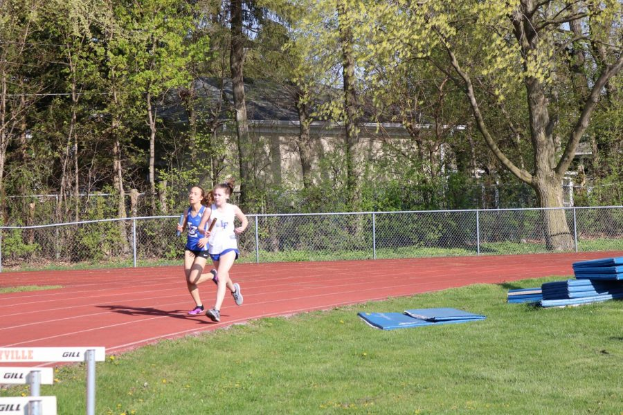 A Lake Zurich runner overtakes a Lake Forest runner around the curve of the oval track on their leg of the 4 x 800 meter relay race.