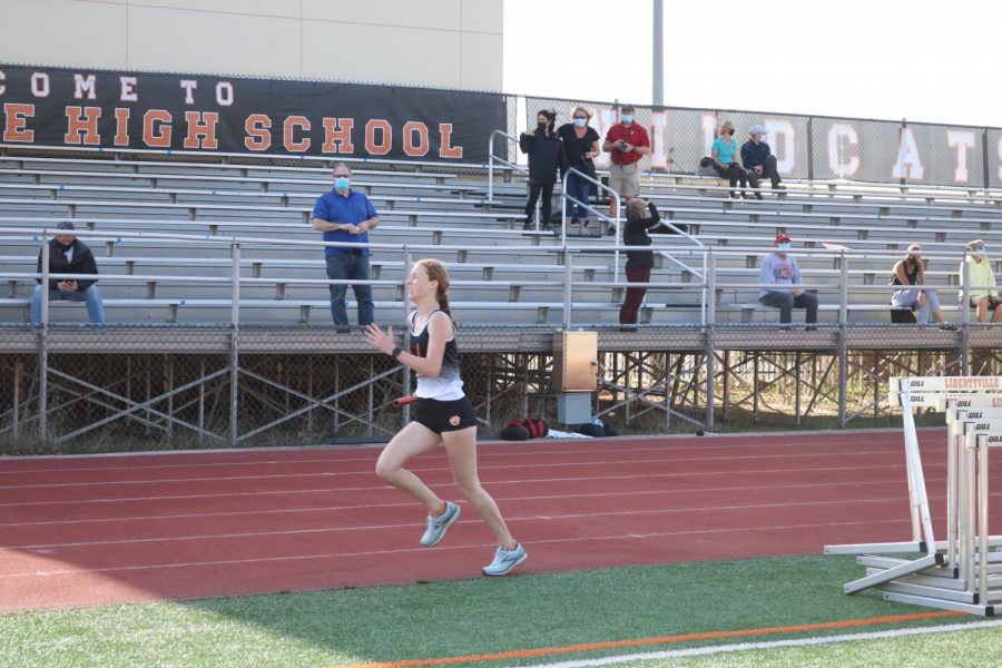 Junior varsity team member Payton Grana finishes the second of her two laps around the track in the longest relay to the cheers of her teammates.