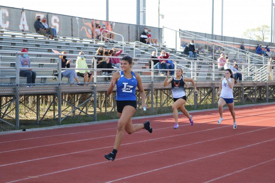 A Lake Zurich runner takes the lead in stride as she finishes her leg of the 4 x 200 relay race. LHS runner Dakota Lyons runs behind in a close second.