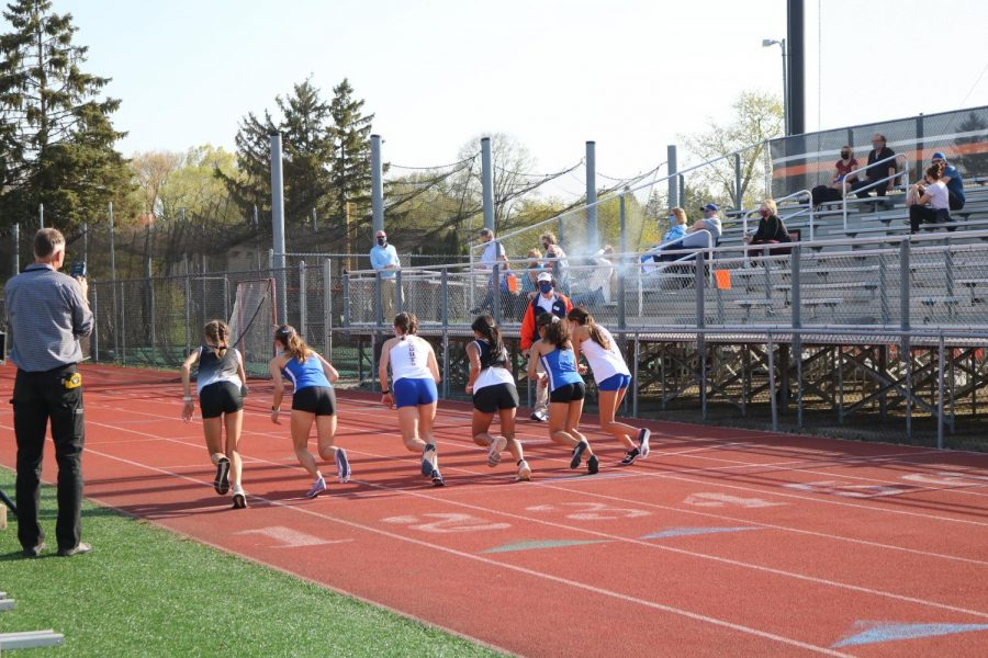 Two runners from each team compete in the 100 meter dash as the starter pistol goes off to signify the beginning of the race.