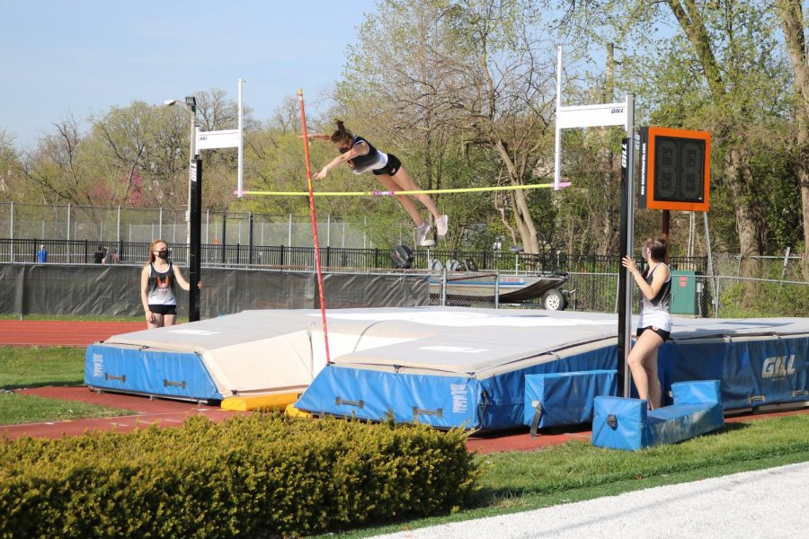 Rachel Birch cleanly clears the bar in the pole vault with her teammates watching her form from the sides.