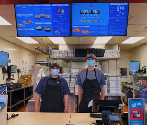 Edder (on the left), the Domino's manager, encourages people to apply to work at the restaurant, as they are hiring. Brian Brzezinski (on the right) is a Domino's employee standing next to him.