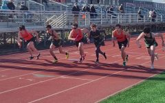 LHS runners (from left to right, in orange) Danny Woja, Gabe Banek and Andrew Brooks are spaced out among Stevenson runners to start the first leg of the 4x800 relay.
