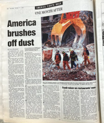 """""""America Brushes Off Dust"""" - a newspaper article covering the aftermath of 9/11 provided by Mr. O'Neill who collected months-worth of articles covering the 9/11 attack."""