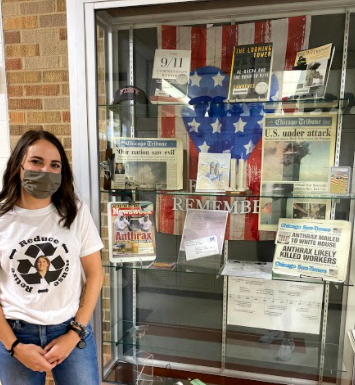 Mrs. Greenswag stands beside the 9/11 display case after discussing her timeline of how Al Qaeda came into power, the influence of foreign countries on Afghanistan, and the history of Afghanistan. The Social Studies Department shared this timeline with their classes.