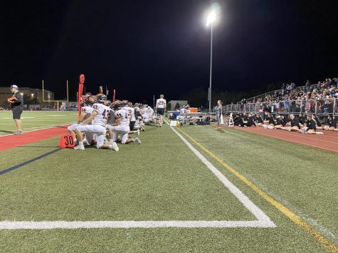 The team kneels as their quarterback Connor Dickson is down on the field.