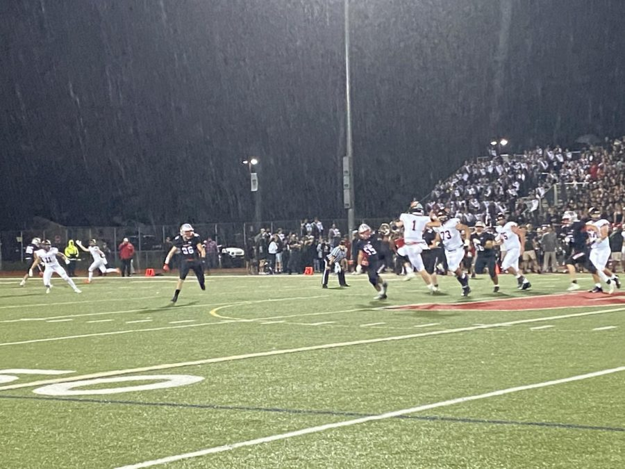 Connor Dickson (1) leaps to complete a pass to Brett Scheuneman (11) as rain falls in the late 4th quarter.