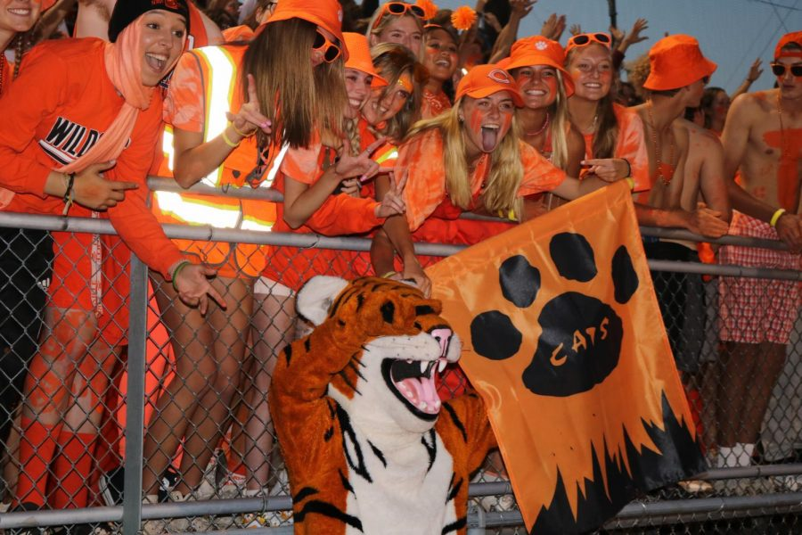 Seniors show their pride with Willy the Wildcat and swing the school's flag. The first home football game theme was 'orange out', and every person was covered in orange to show their Wildcat spirit.