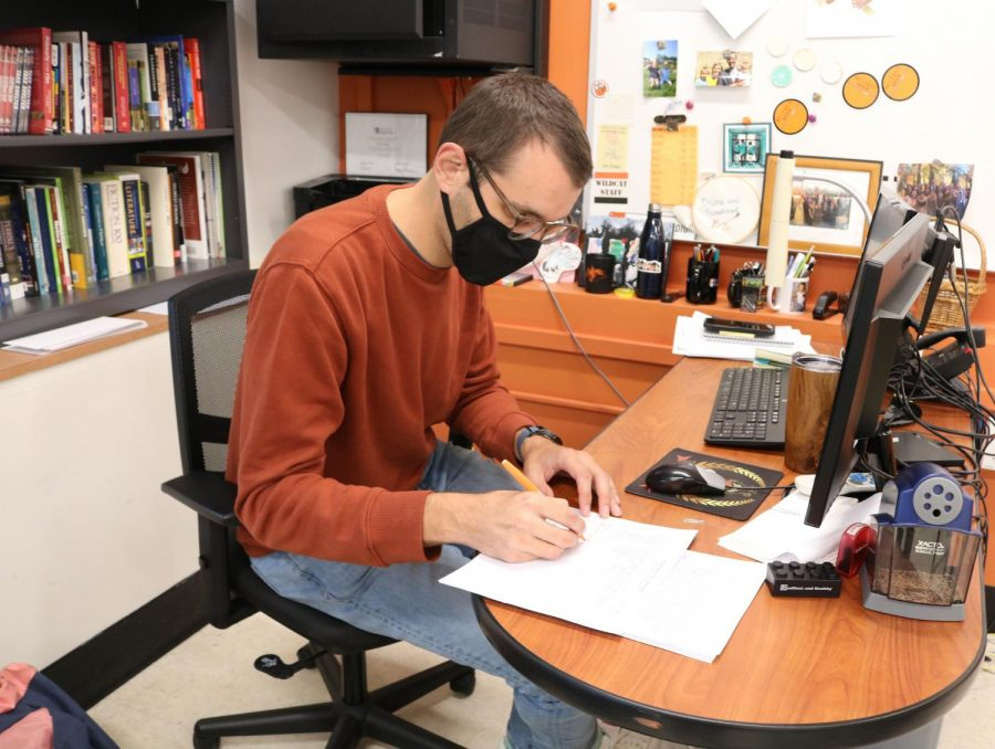 English teacher Ryan Ebling grades student assignments while utilizing new grading practices. He is using a rubric that grades students on a scale from one to five.