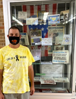 Mr. O'Neill stands beside his display case showcasing artifacts from the months preceding the 9/11 attack. The display case included: newspapers, books, diagrams, and the American flag.