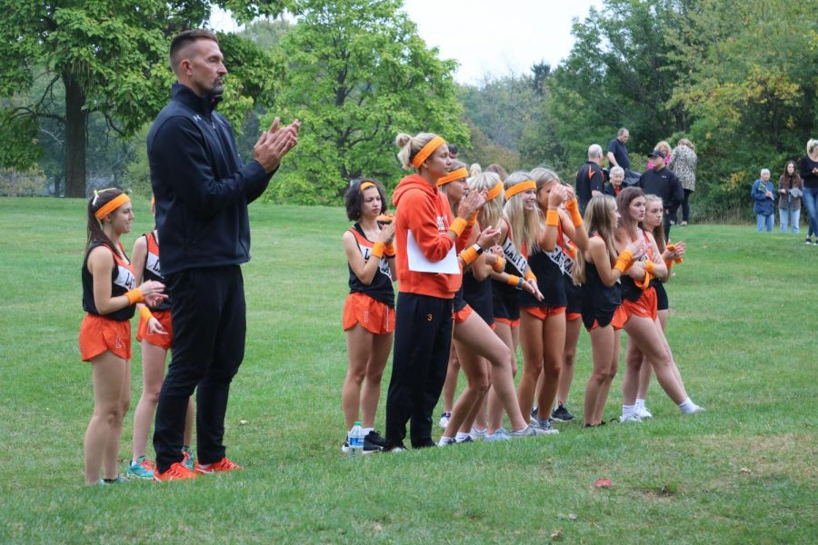 Athletic Director John Woods and the girls team cheer on the boys cross country team during their race.