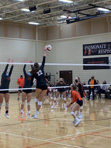Keira Kasten (22) flies above the net for a spike.