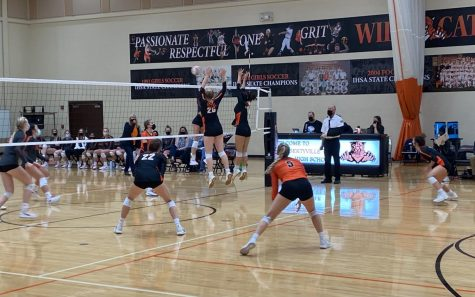 Kelly Hutchins (26) and Margot Kauffman (13) jump for the block while Keira Kasten (22), Grace Comilla (5) and Grace Bonjour (18) prepare for a deflection.