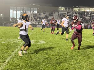Connor Dickson (1) drops back to pass with a Mundeleien defender applying heavy pressure.
