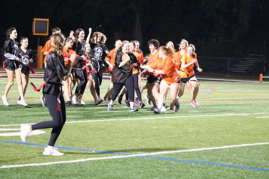 Libby Karston runs down the field while her team cheers her along.